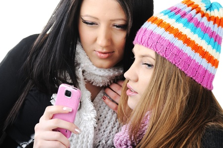 Two female friends reading sms message on cell phone photo