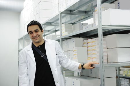 Young cheerful worker in modern drug warehouse photo