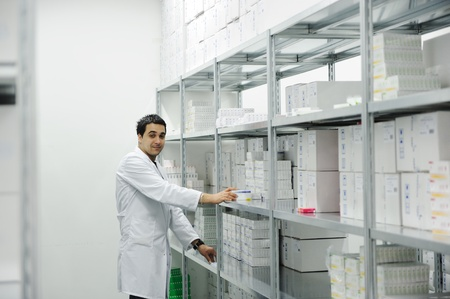 pill box: Worker putting boxes together on shelves in modern warehouse