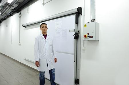 abriendo puerta: Joven trabajador de apertura de la puerta del refrigerador industrial Foto de archivo