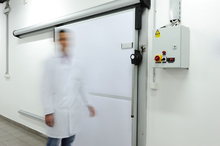 cold storage: Young worker opening  door of industrial refrigerator, speed motion Stock Photo