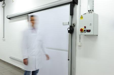 Young worker opening  door of industrial refrigerator, speed motion photo