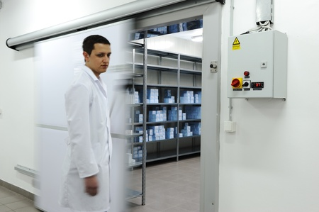 Young worker opening  door of industrial refrigerator  photo