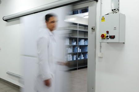 male sperm: Young worker opening  door of industrial refrigerator, blurred motion