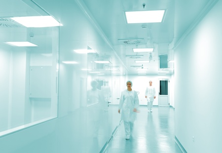 Modern bright factory interior with working people in motion photo
