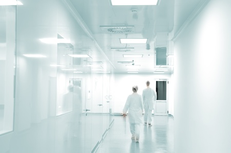 laboratory research: Working people with white uniforms walking in modern  factory environment
