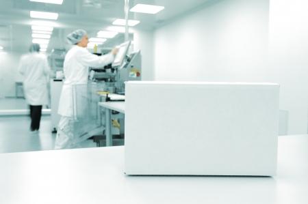 nettoyer: Bo�te blanche � la ligne de production automatis�e � l'usine moderne, les personnes qui travaillent en arri�re-plan Banque d'images