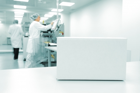food industry: White box at automated production line at modern factory, people working in background Stock Photo