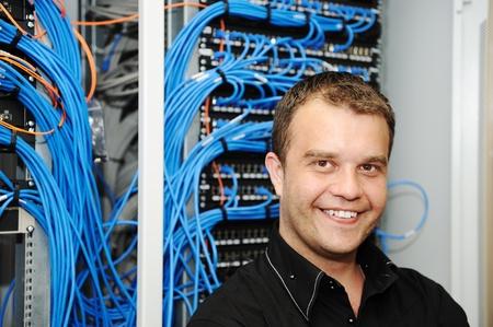 cable red: Administrador en sala de servidores Foto de archivo