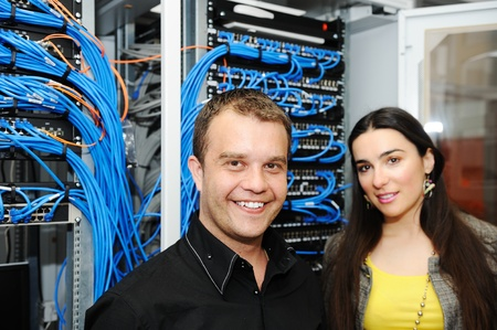 female engineer: Two administrators, male and female, at server room Stock Photo