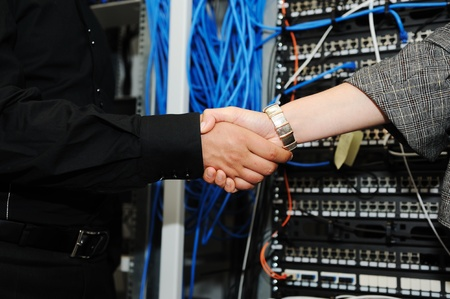 Handshaking at server room, man and woman photo