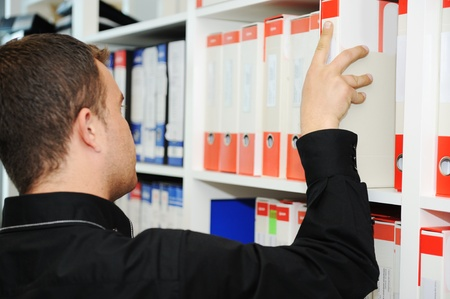 single shelf: Man working at office putting folders together on shelves
