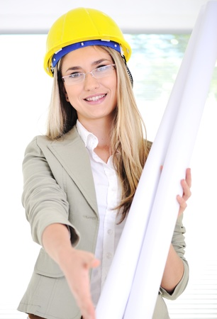 female construction worker: Female engineer with blueprints shaking your hand