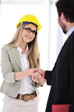 Businessman and female engineer making a deal at office photo