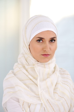 Young beautiful Muslim woman with traditional but fashionable clothes photo