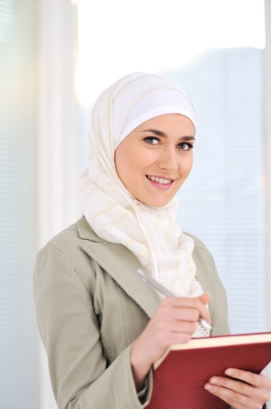 arabic woman: Muslim Caucasian female student with notebook and pen