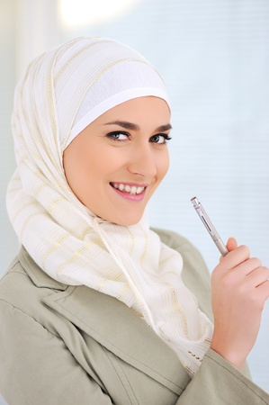 learning arabic: Muslim Caucasian female student holding pen Stock Photo