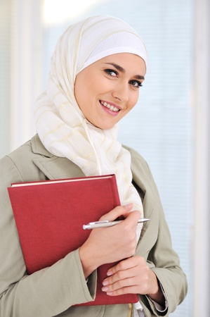 muslim: Muslim Caucasian female student with notebook and pen