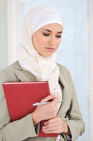 learning arabic: Muslim Caucasian female student with notebook and pen