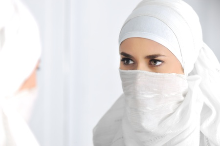 Beautiful Muslim woman looking at mirror Stock Photo