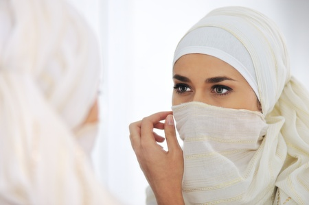 Beautiful Muslim woman looking at mirror and putting her scarf photo