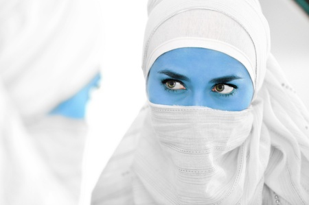 Muslim woman with blue skin as alien or avatar looking at mirror, conceptual image photo