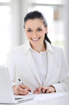 Portrait of cute young business woman smiling and working at the desk in office photo