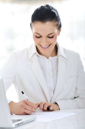 Happy business woman signing documents at office Stock Photo - 12627440