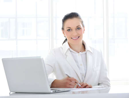 Young business woman at office with laptop photo