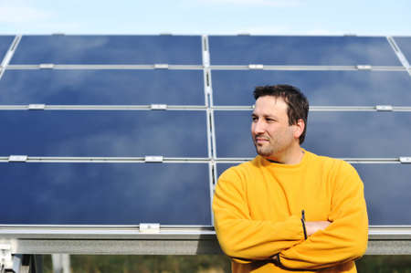 Young male worker with solar panels in background photo