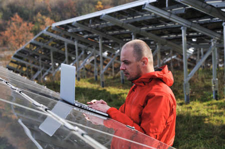 Male engineer using laptop, solar panels in background photo