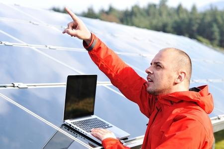 radiacion solar: Ingeniero de Mujer con ordenador portátil, los paneles solares en el fondo Foto de archivo