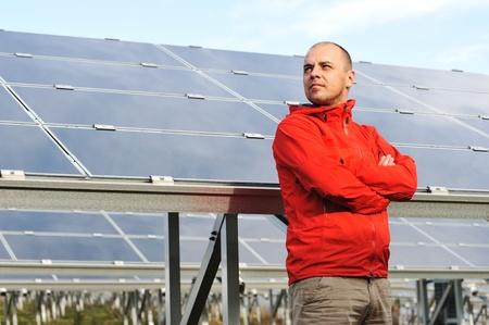 radiacion solar: Joven trabajador de sexo masculino con paneles solares en el fondo Foto de archivo