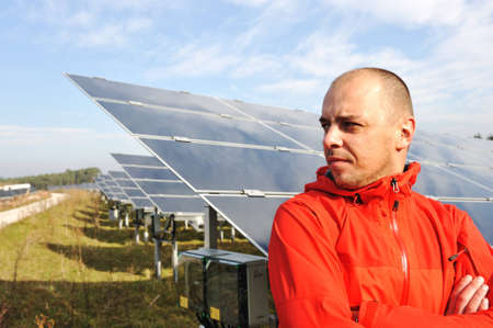 radiacion solar: Joven ingeniero macho con paneles solares en el fondo