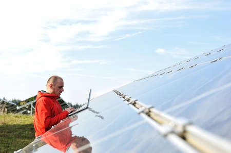 Male engineer at work place, solar panels in background Stock Photo - 12627636