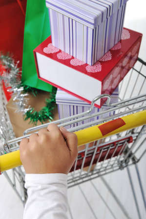 Woman in shoping pushing cart with bags and boxes photo
