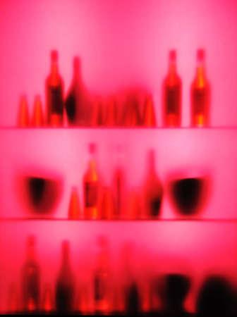 handle bars: Abstract blurred vine bottles and glasses on shelf, pink color