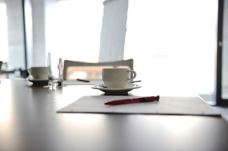 office notes: Cup of coffee on table in the conference room