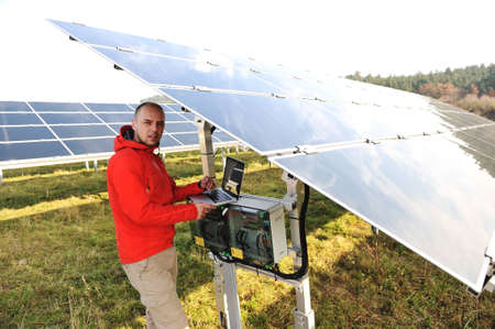 Engineer working with laptop by solar panels Stock Photo - 12627131
