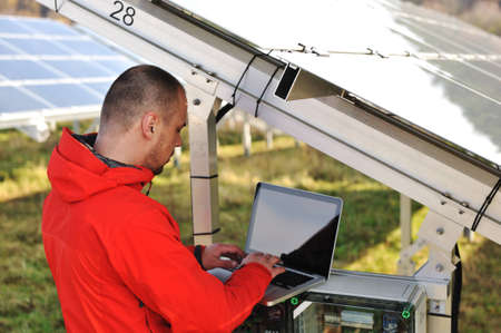 setup man: Engineer working with laptop by solar panels  Stock Photo