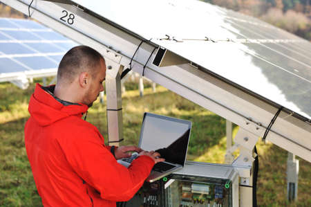Engineer working with laptop by solar panels Stock Photo - 12627312