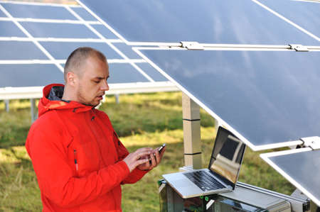 Engineer working with laptop by solar panels, talking on cell phone Stock Photo - 12627261