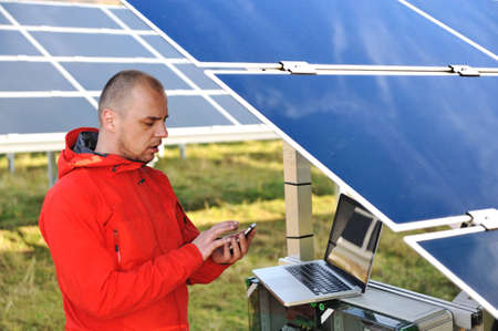 Engineer working with laptop by solar panels, talking on cell phone Stock Photo - 12627225