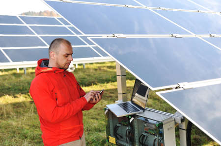 Engineer working with laptop by solar panels, talking on cell phone photo