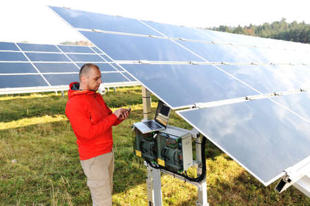setup man: Engineer working with laptop by solar panels, talking on cell phone Stock Photo