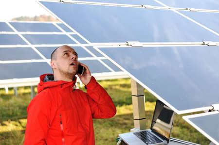 radiacion solar: Ingeniero trabajando con el ordenador portátil por paneles solares, hablando por teléfono celular