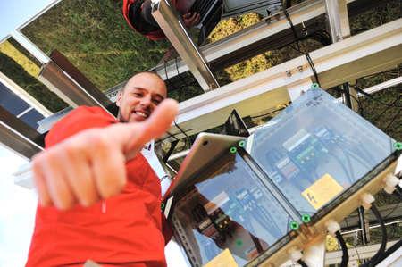 radiacion solar: Ingeniero trabajando con la computadora portátil la instalación de paneles solares Foto de archivo