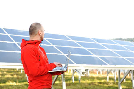 Male engineer using laptop, solar panels in background Stock Photo - 12627633