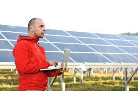 Male engineer using laptop, solar panels in background Stock Photo - 12627608