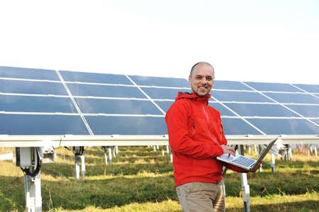 radiacion solar: Ingeniero trabajando con portátiles, paneles solares en el fondo